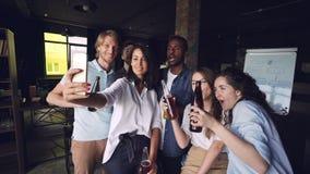 Η όμορφη κυρία παίρνει selfie με τους συναδέλφους χρησιμοποιώντας το smartphone, η πολυ-εθνική ομάδα ανθρώπων θέτει με τα ποτά κα απόθεμα βίντεο