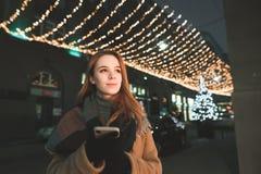 Η όμορφη κυρία στα θερμά ενδύματα στέκεται με ένα smartphone στα χέρια της στο υπόβαθρο μιας οδού νύχτας στοκ εικόνες με δικαίωμα ελεύθερης χρήσης