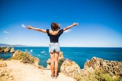 Η όμορφη λατινική στάση γυναικών σε έναν βράχο επάνω από τον ωκεανό και χαιρετίζει το καλοκαίρι Στοκ φωτογραφίες με δικαίωμα ελεύθερης χρήσης