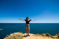 Η όμορφη λατινική στάση γυναικών σε έναν βράχο επάνω από τον ωκεανό και χαιρετίζει το καλοκαίρι Στοκ Εικόνες