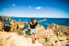 Η όμορφη λατινική στάση γυναικών σε έναν βράχο επάνω από τον ωκεανό και χαιρετίζει το καλοκαίρι Στοκ εικόνα με δικαίωμα ελεύθερης χρήσης