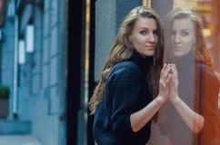 Η όμορφη λεπτή γυναίκα στέκεται μπροστά από την προθήκη Στοκ εικόνες με δικαίωμα ελεύθερης χρήσης