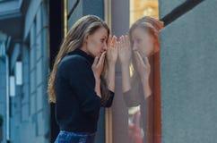 Η όμορφη λεπτή γυναίκα στέκεται μπροστά από την προθήκη Στοκ φωτογραφία με δικαίωμα ελεύθερης χρήσης
