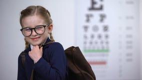 Η όμορφη μαθήτρια στα γυαλιά χαμογελά, συνειδητοποίηση της πλήρους εξέτασης οφθαλμών ενώπιον του σχολείου φιλμ μικρού μήκους