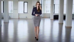 Η όμορφη μακρυμάλλης επιχειρησιακή γυναίκα που ντύνεται στην μπλε μπλούζα, την γκρίζα φούστα και τα ψηλοτάκουνα παπούτσια περπατά φιλμ μικρού μήκους
