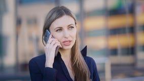 Η όμορφη μακρυμάλλης επιχειρησιακή γυναίκα στέκεται στην οδό κοντά στο κτίριο γραφείων και μιλά στο τηλέφωνο θηλυκό απόθεμα βίντεο