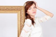 Η όμορφη μελαγχολική γυναίκα στο φόρεμα στέκεται κοντά στο πλαίσιο Στοκ Φωτογραφίες