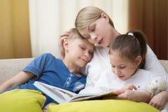 Η όμορφη μητέρα διαβάζει ένα βιβλίο στα μικρά παιδιά της Η αδελφή και ο αδελφός ακούνε μια ιστορία στοκ εικόνα