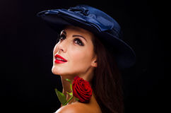 Η όμορφη, μοντέρνη γυναίκα που φορά ένα καπέλο και που χαμογελά αυξήθηκε Στοκ Φωτογραφίες
