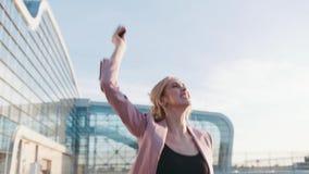 Η όμορφη μοντέρνη νέα γυναίκα σε μια βιασύνη περπατά στο επιχειρησιακό κέντρο, και χρησιμοποιεί το τηλέφωνό της, λαμβάνει το μήνυ απόθεμα βίντεο