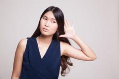 Η όμορφη νέα ασιατική γυναίκα ακούει κάτι Στοκ φωτογραφία με δικαίωμα ελεύθερης χρήσης
