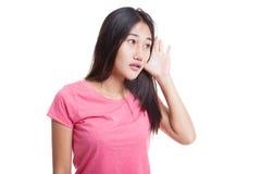 Η όμορφη νέα ασιατική γυναίκα ακούει κάτι Στοκ Εικόνα