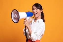 Η όμορφη νέα ασιατική γυναίκα αναγγέλλει με megaphone στοκ εικόνα
