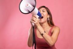 Η όμορφη νέα ασιατική γυναίκα αναγγέλλει με megaphone στοκ φωτογραφία