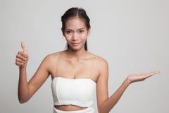 Η όμορφη νέα ασιατική γυναίκα παρουσιάζει το χέρι και αντίχειρες παλαμών Στοκ Εικόνες