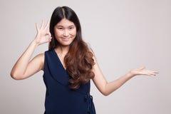 Η όμορφη νέα ασιατική γυναίκα παρουσιάζει το χέρι παλαμών και ΕΝΤΑΞΕΙ σημάδι Στοκ Φωτογραφία