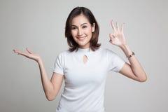 Η όμορφη νέα ασιατική γυναίκα παρουσιάζει το χέρι παλαμών και ΕΝΤΑΞΕΙ σημάδι Στοκ φωτογραφία με δικαίωμα ελεύθερης χρήσης
