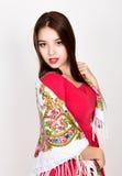 Η όμορφη νέα γυναίκα έντυσε σε ένα κόκκινο φόρεμα και χρωμάτισε την τοποθέτηση μαντίλι στο στούντιο Στοκ εικόνες με δικαίωμα ελεύθερης χρήσης