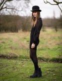 Η όμορφη νέα γυναίκα έντυσε στο μαύρο φορώντας καπέλο σφαιριστών στοκ εικόνα