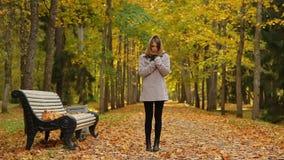Η όμορφη νέα γυναίκα αισθάνεται κρύα στεμένος κοντά σε έναν πάγκο στο πάρκο φθινοπώρου απόθεμα βίντεο