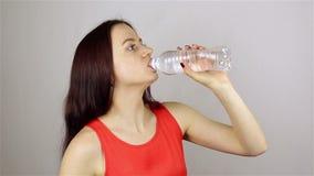 Η όμορφη νέα γυναίκα ανοίγει ένα μπουκάλι και πίνει το νερό απόθεμα βίντεο
