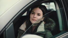 Η όμορφη νέα γυναίκα αυξάνει το γυαλί της πόρτας του αυτοκινήτου της απόθεμα βίντεο