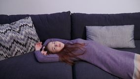 Η όμορφη νέα γυναίκα βρίσκεται στον καναπέ στο καθιστικό και εξετάζει τη κάμερα φιλμ μικρού μήκους