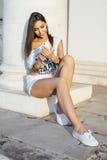 Η όμορφη νέα γυναίκα γράφει ένα μήνυμα στο τηλέφωνο, στην άσπρα μπλούζα και τα σορτς, το μακρυμάλλες brunette, κοινωνική δικτύωση Στοκ Φωτογραφία