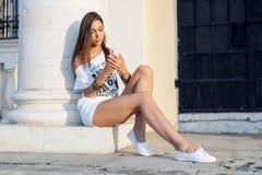 Η όμορφη νέα γυναίκα γράφει ένα μήνυμα στο τηλέφωνο, στην άσπρα μπλούζα και τα σορτς, το μακρυμάλλες brunette, κοινωνική δικτύωση Στοκ Εικόνα