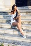 Η όμορφη νέα γυναίκα γράφει ένα μήνυμα στο τηλέφωνο, στην άσπρα μπλούζα και τα σορτς, το μακρυμάλλες brunette, κοινωνική δικτύωση Στοκ Εικόνες