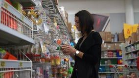 Η όμορφη νέα γυναίκα επιλέγει έναν ειρηνιστή για το παιδί στην υπεραγορά φιλμ μικρού μήκους