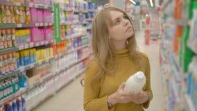 Η όμορφη νέα γυναίκα επιλέγει τα οικιακά προϊόντα κάνοντας τις αγορές στην υπεραγορά απόθεμα βίντεο