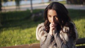 Η όμορφη νέα γυναίκα κάθεται σε έναν πάγκο σε ένα πάρκο φθινοπώρου φιλμ μικρού μήκους