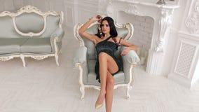 Η όμορφη νέα γυναίκα κάθεται σε μια καρέκλα με το φίδι φιλμ μικρού μήκους