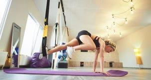 Η όμορφη νέα γυναίκα κάνει μια σκληρή άσκηση για το τέντωμα των ποδιών σε ένα στούντιο γιόγκας αυτή χρησιμοποιώντας μια υποστήριξ φιλμ μικρού μήκους