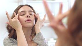 Η όμορφη νέα γυναίκα κάνει το του προσώπου δέρμα μασάζ με τον μπροστινό καθρέφτη λουτρών δάχτυλων φιλμ μικρού μήκους