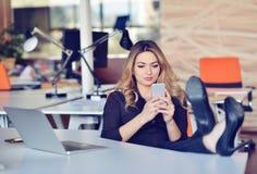 Η όμορφη νέα γυναίκα κάνει selfie στον εργασιακό χώρο της Χαλαρώνει και βάζει τα πόδια της στον πίνακα Στοκ Φωτογραφίες