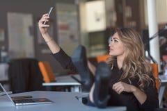 Η όμορφη νέα γυναίκα κάνει selfie στον εργασιακό χώρο της Χαλαρώνει και βάζει τα πόδια της στον πίνακα Στοκ εικόνες με δικαίωμα ελεύθερης χρήσης