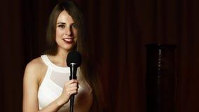 Η όμορφη νέα γυναίκα κρατά mic, εξετάζει τη κάμερα και τραγουδά με το ακτινοβόλο χαμόγελο απόθεμα βίντεο