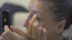 Η όμορφη νέα γυναίκα μαδά τα φρύδια, κινηματογράφηση σε πρώτο πλάνο απόθεμα βίντεο