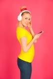 Η όμορφη νέα γυναίκα με τα μεγάλα ακουστικά ακούει τη μουσική ο Στοκ φωτογραφίες με δικαίωμα ελεύθερης χρήσης