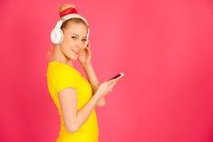 Η όμορφη νέα γυναίκα με τα μεγάλα ακουστικά ακούει τη μουσική ο Στοκ φωτογραφία με δικαίωμα ελεύθερης χρήσης
