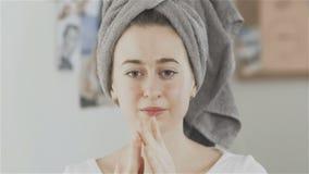Η όμορφη νέα γυναίκα με την πετσέτα στο κεφάλι που εφαρμόζει την κρέμα στο πρόσωπο και εξετάζει τη κάμερα απόθεμα βίντεο