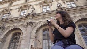 Η όμορφη νέα γυναίκα με τη σκοτεινή τρίχα, που φορά τα τζιν και τη μαύρη μπλούζα παίρνει τις εικόνες της πόλης Αριστερό στο σωστό φιλμ μικρού μήκους