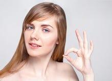 Η όμορφη νέα γυναίκα με τη σύνθεση παρουσιάζει εντάξει χειρονομία στοκ φωτογραφίες με δικαίωμα ελεύθερης χρήσης