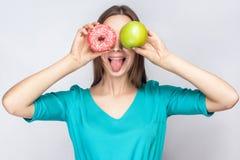 Η όμορφη νέα γυναίκα με τις φακίδες στο πράσινο φόρεμα, που κρατά πριν από τα μάτια της το πράσινο μήλο και ρόδινο doughnut και π Στοκ Εικόνα