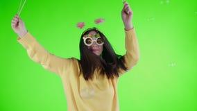 Η όμορφη νέα γυναίκα με το αστεία καπέλο και τα γυαλιά είναι χορός μόνο σε μια πράσινη οθόνη φιλμ μικρού μήκους