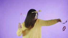 Η όμορφη νέα γυναίκα με το αστεία καπέλο και τα γυαλιά είναι χορός μόνο σε ένα πορφυρό υπόβαθρο απόθεμα βίντεο