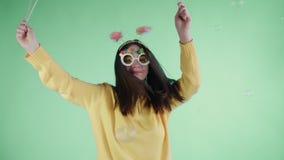 Η όμορφη νέα γυναίκα με το αστεία καπέλο και τα γυαλιά είναι χορός μόνο σε ένα πράσινο υπόβαθρο απόθεμα βίντεο