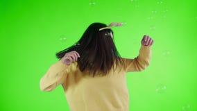 Η όμορφη νέα γυναίκα με το αστείο καπέλο είναι χορός με τις φυσαλίδες σαπουνιών σε μια πράσινη οθόνη απόθεμα βίντεο